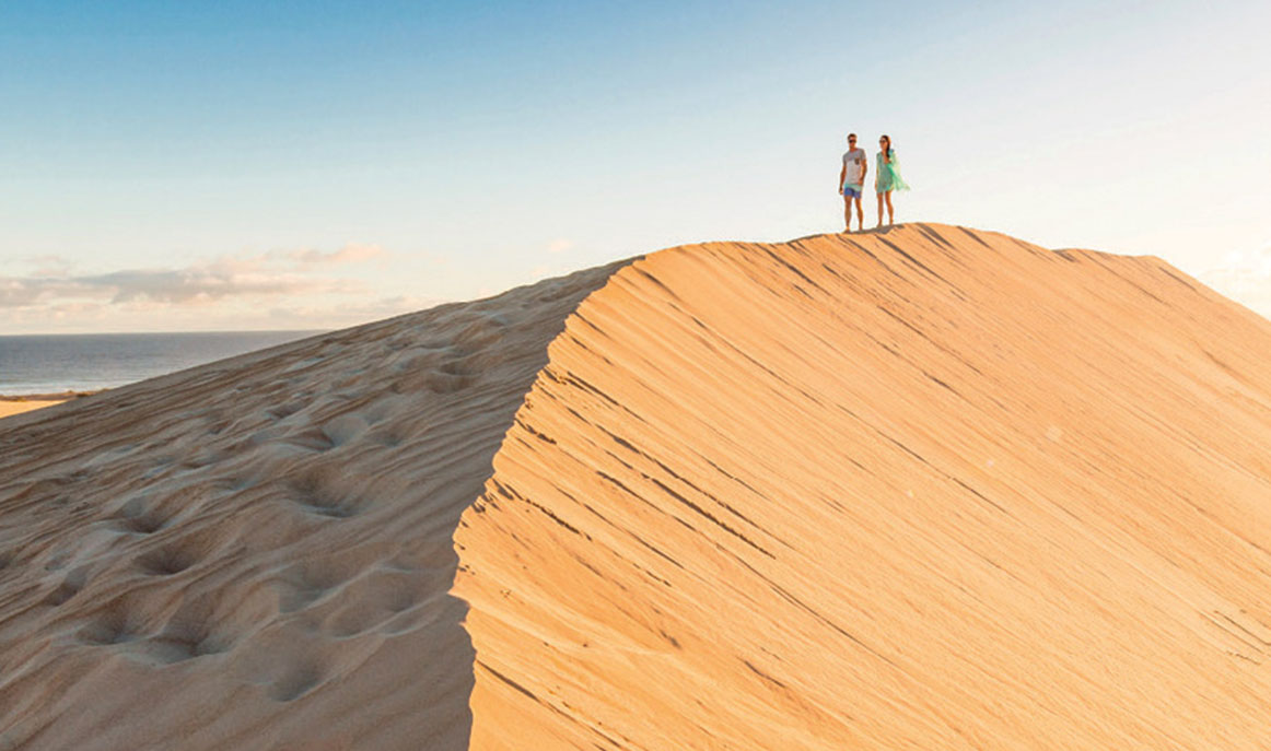 Two people walk along the ridge of a lone sand dune