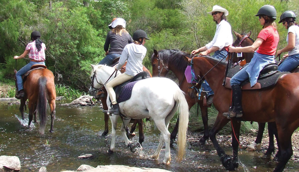 Group of horseriders cross a shallow water crossing