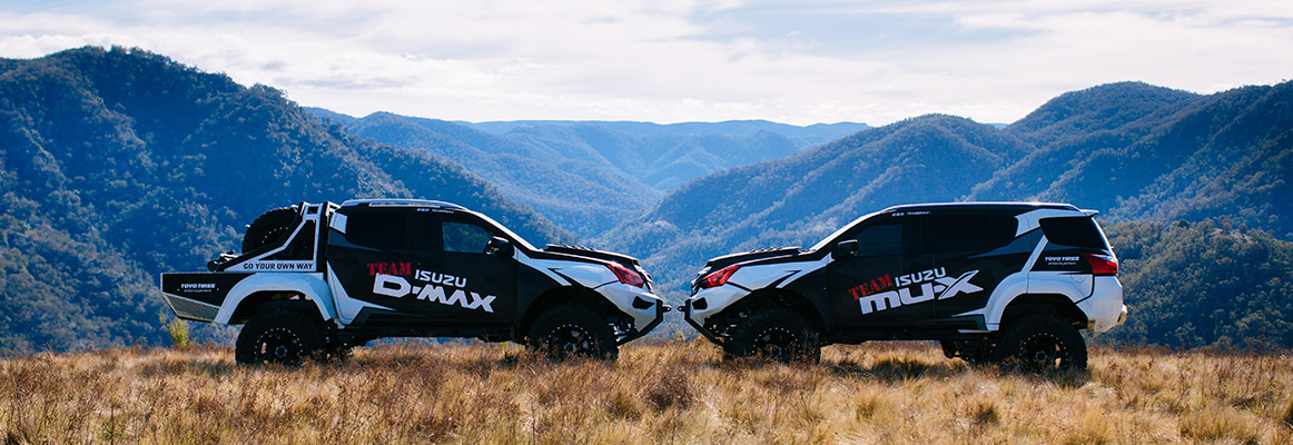 Two Concept-X Team Isuzu Utes parked on a cliff