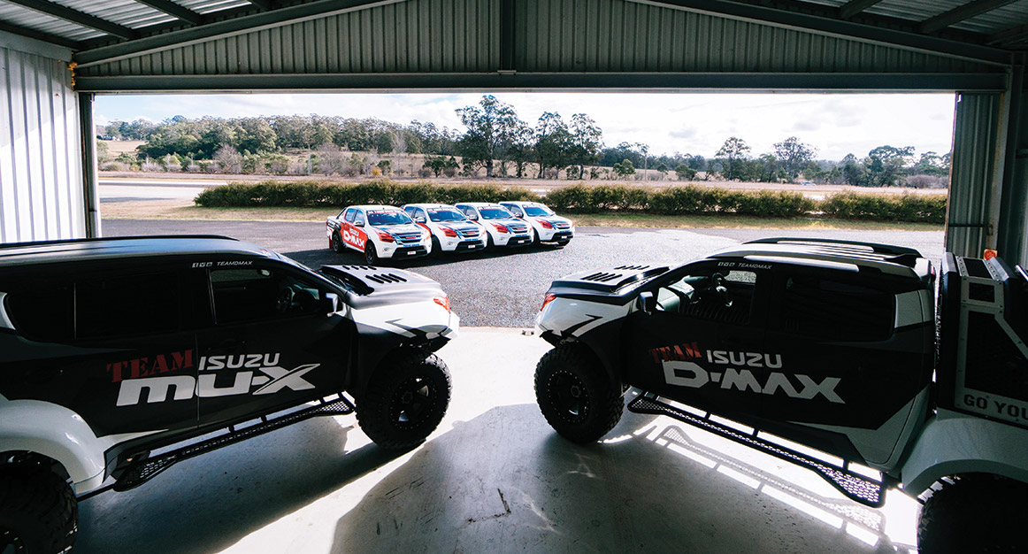 Concept-X Team Isuzu vehicles parked in large shed