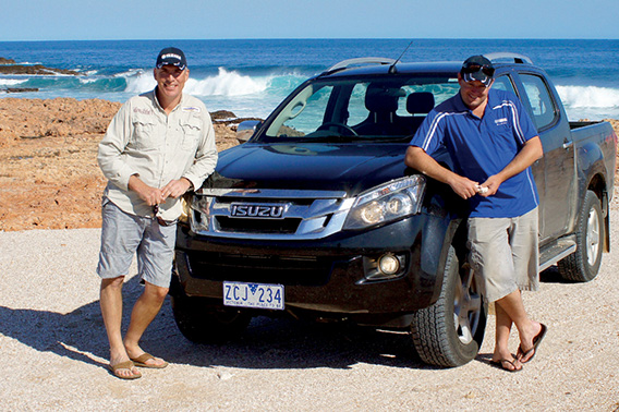 Nick Duigan and Andrew Hart lean against their D-MAX next to the ocean